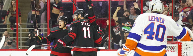 The Hurricanes' Sebastian Aho (obstructed) is congratulated by teammates Jordan Staal and Teuvo Teravainen after his first-period goal against the New York Islanders in Game 4 of their second-round playoff series on May 3, 2019 in Raleigh, North Carolina.