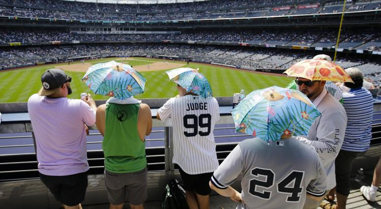 Fans use umbrella hats to protect themselves from the sun during the sixth inning of a baseball game between the New York Yankees and the Colorado Rockies Saturday, July 20, 2019, in New York.