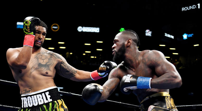 Deontay Wilder (bronze trunks) trades punches with Dominic Breazeale (green trunks) in the first round of a world heavyweight championship boxing match at Barclays Center.