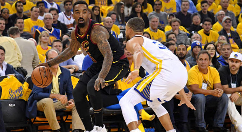The Cavaliers' J.R. Smith dribbles while being defended by the Warriors' Stephen Curry.