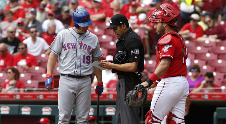 The Mets' Jay Bruce looks over the lineup card with home plate umpire Gabe Morales during the first inning on May 9, 2018, at Great American Ball Park in Cincinnati.