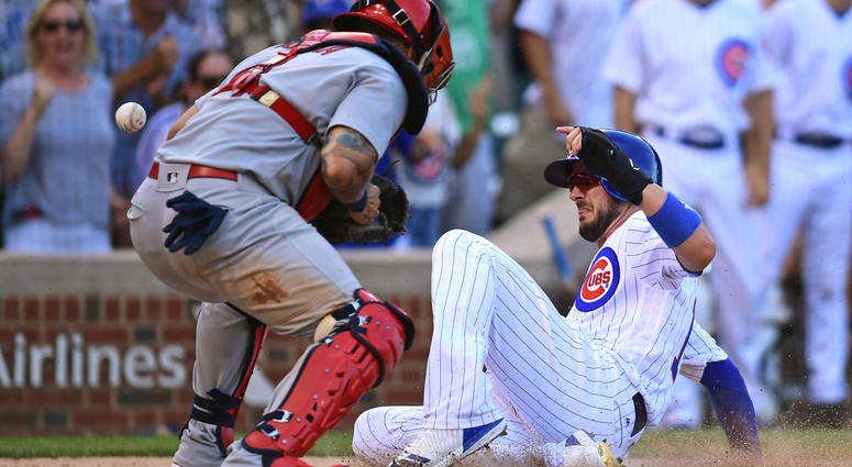 Jul 22, 2017; Chicago, IL, USA; Chicago Cubs third baseman Kris Bryant (right) slides safely into home plate to score against St. Louis Cardinals catcher Yadier Molina (left) in the eighth inning at Wrigley Field.Mandatory Credit: Patrick Gorski-USA TODAY