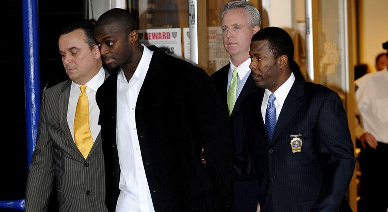 Plaxico Burress is led to a squad car for transport to his arraignment outside the NYPD 17th Precinct on Dec. 1, 2008.