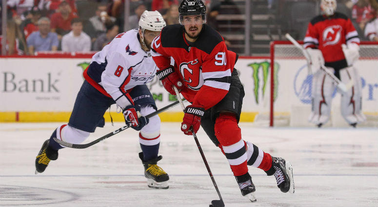 Marcus Johansson skates with the puck while being pursued by Alex Ovechkin during the second period at Prudential Center.