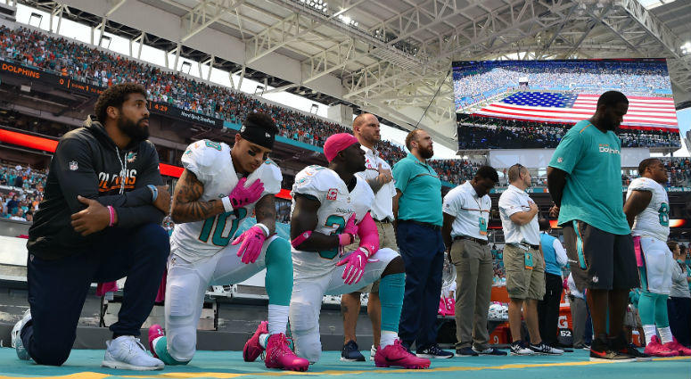 Arian Foster, Kenny Stills and Michael Thomas kneel during the National Anthem before the game against the Tennessee Titans at Hard Rock Stadium in Miami.