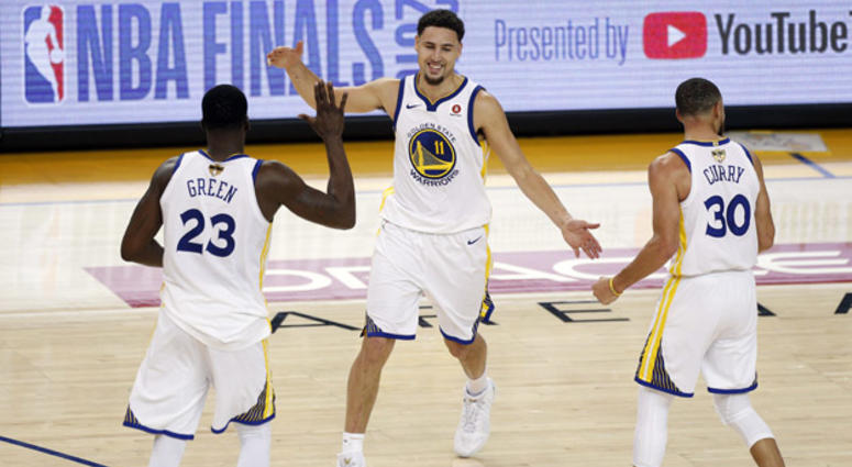 Golden State Warriors guard Klay Thompson (11) reacts with forward Draymond Green (23) and guard Stephen Curry during overtime in Game 1 of the NBA Finals on May 31, 2018, at Oracle Arena in Oakland, California.