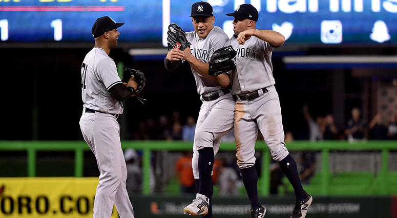 New York Yankees right fielder Giancarlo Stanton (center) celebrates with Yankees left fielder Brett Gardner (right) and Yankees center fielder Aaron Hicks (left) after the Yankees defeating the Miami Marlins at Marlins Park on Aug 21, 2018.