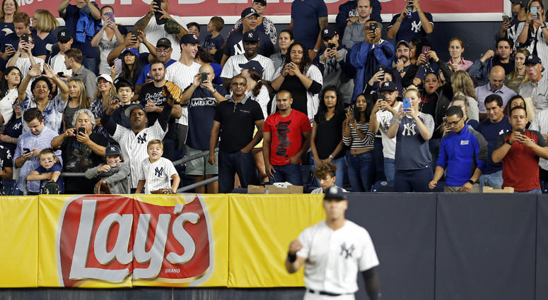 Fans take photos of Yankees right fielder Aaron Judge as he warms up against the Toronto Blue Jays during the eighth inning on Sept. 14, 2018, at Yankee Stadium.