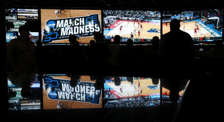 In this March 15, 2018 photo, people watch coverage of the first round of the NCAA college basketball tournament at the Westgate Superbook sports book in Las Vegas.