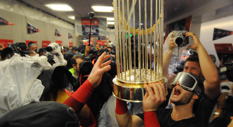 Boston Red Sox players celebrate with the Commissioner's Trophy in the clubhouse after defeating the Los Angeles Dodgers in game five of the 2018 World Series at Dodger Stadium.