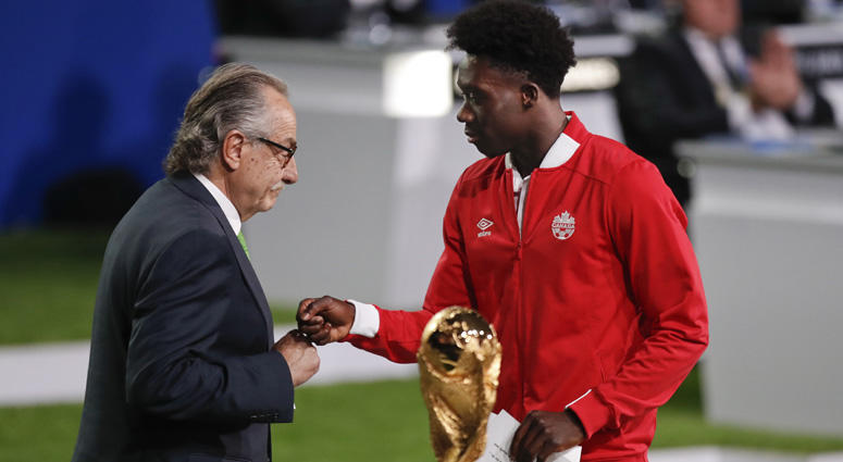 Decio de Maria, president of the Football Association of Mexico (left) and Canadian soccer player Alphonso Davies present a joint bid by Canada, Mexico and the United States to host the 2026 World Cup at the FIFA congress in Moscow on June 13, 2018.