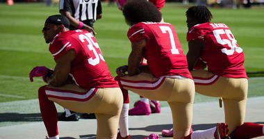 Three 49ers players, including Colin Kaepernick (7), kneel during the national anthem before a 2016 game.