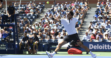 Roger Federer, of Switzerland, returns a shot to Daniel Evans, of the United Kingdom, during round three of the US Open tennis championships Friday, Aug. 30, 2019, in New York
