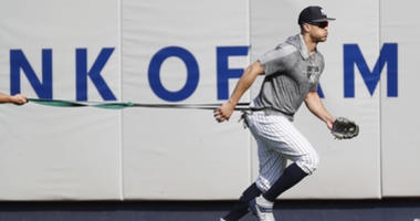 New York Yankees' Giancarlo Stanton, who has been out the much of the season with various injuries, trains with a resistance band in the outfield before a baseball game between the Yankees and the Texas Rangers, Wednesday, Sept. 4, 2019, in New York