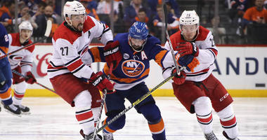 The Hurricanes' Justin Faulk (27) and Brock McGinn hold up the Islanders' Cal Clutterbuck in Game 1 of the second-round playoff series between the teams on April 26, 2019, at the Barclays Center.