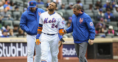Apr 28, 2019; New York City, NY, USA; New York Mets second baseman Robinson Cano (24) is taken out of the game after getting hit by a pitch in the first inning against the Milwaukee Brewers at Citi Field. Mandatory Credit: Wendell Cruz-USA TODAY Sports
