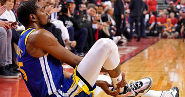 Golden State Warriors forward Kevin Durant sits on the court after an apparent injury in Game 5 of the NBA Finals against the Raptors on June 10, 2019, in Toronto.