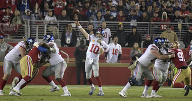 Giants quarterback Eli Manning throws a pass under pressure from San Francisco 49ers defensive tackle DeForest Buckner (99) on Nov. 12, 2018, at Levi's Stadium in Santa Clara, California.