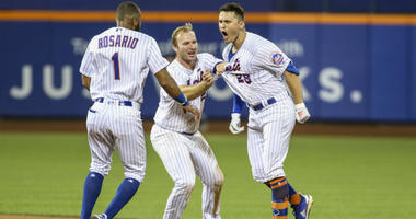 Amed Rosario, Pete Alonso, and J.D. Davis celebrate after another Mets win.