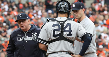 Yankees coach Larry Rothschild (left) leaves the mound following a visit with pitcher James Paxton (right) after Paxton walked the bases loaded against the Orioles on April 4, 2019, at Oriole Park at Camden Yards in Baltimore.