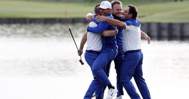 Europe golfer Alex Noren is congratulated by teammates on the 18th green during the Ryder Cup Sunday singles matches at Le Golf National.