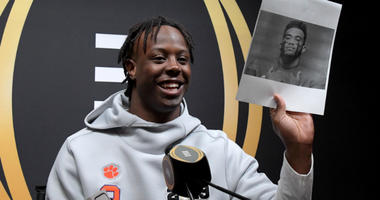 Travis Etienne holds up a picture of Tua Tagovailoa