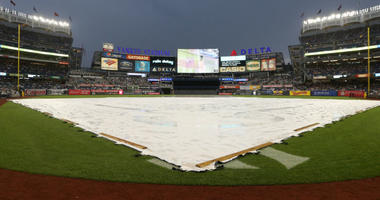 General view of a tarp on the field as the scoreboard at Yankee Stadium informs fans of a rain delay before a game between the New York Yankees and the Kansas City Royals.