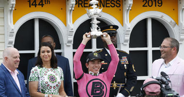 Tyler Gaffalione holds the Woodlawn Vase after winning the 144th running of the Preakness Stakes aboard War of Will at Pimlico Race Course.