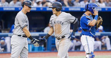 The Yankees' Gio Urshela celebrates his second home run of the game with teammate DJ LeMahieu on Aug. 8, 2019, against the Blue Jays at the Rogers Centre in Toronto.