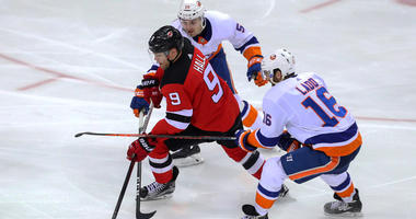 Devils left wing Taylor Hall skates with the puck between Islanders left wing Andrew Ladd (16) and defenseman Adam Pelech on March 31, 2018, at Prudential Center.