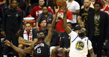 The Rockets' Clint Capela (15) plays for the ball against the Warriors' Draymond Green (23) during Game 2 of the Western Conference finals on May 16, 2018, at the Toyota Center in Houston.