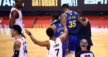 The Warriors' Kevin Durant is assisted off the court after sustaining an injury against the Toronto Raptors during Game 5 of the NBA Finals on June 10, 2019, at Scotiabank Arena in Toronto.