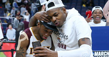 Iona Gaels guard Rickey McGill (left) and forward Tajuan Agee (right) celebrate following the MAAC Conference Tournament Championship game against the Monmouth Hawks at the Times Union Center in Albany on March 11, 2019.