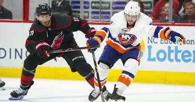 Islanders defenseman Thomas Hickey skates with the puck as Carolina Hurricanes center Jordan Staal chases during Game 3 of their second-round playoff series on May 1, 2019, at the PNC Arena in Raleigh, North Carolina.