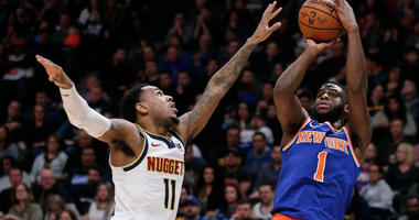 Knicks guard Emmanuel Mudiay shoots against Denver Nuggets guard Monte Morris on Jan. 1, 2019, at the Pepsi Center in Denver.