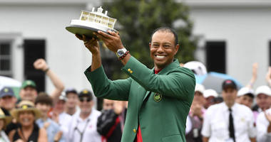 Tiger Woods celebrates with the green jacket and trophy after winning the Masters on April 14, 2019, at Augusta National Golf Club.