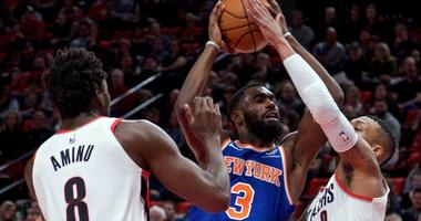 The Knicks' Tim Hardaway Jr. shoots over the Trail Blazers' Damian Lillard (0) and forward Al-Farouq Aminu on March 6, 2018, at the Moda Center in Portland, Oregon.