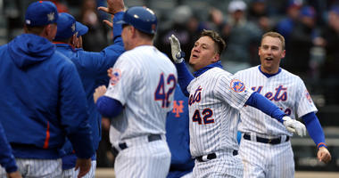 The Mets' Wilmer Flores celebrates with teammates after hitting a walk-off solo home run to beat the Milwaukee Brewers on April 15, 2018, at Citi Field.