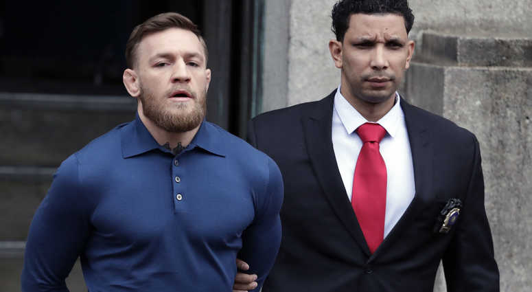 Ultimate fighting star Conor McGregor, left, is led by an official to an unmarked vehicle while leaving the 78th Precinct of the New York Police Department, Friday, April 6, 2018, in the Brooklyn borough of New York. McGregor is facing criminal charges in