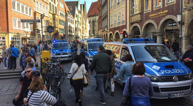 Police vans stand in downtown Muenster, Germany, Saturday, April 7, 2018. German news agency dpa says several people killed after car crashes into crowd in city of Muenster.