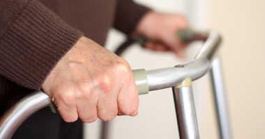 An elderly person using a walker.