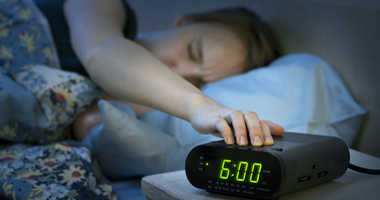 Woman uses an alarm clock.