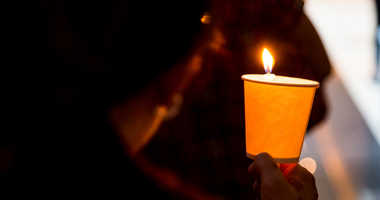 A mourner holds a candle at a vigil.
