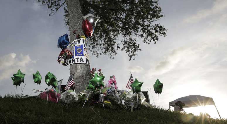 Television newscasters prepare to give updates near a memorial in front of Santa Fe High School on Sunday, May 20, 2018 in Santa Fe, Texas, where a student shot and killed eight classmates and two teachers at Santa Fe High School.
