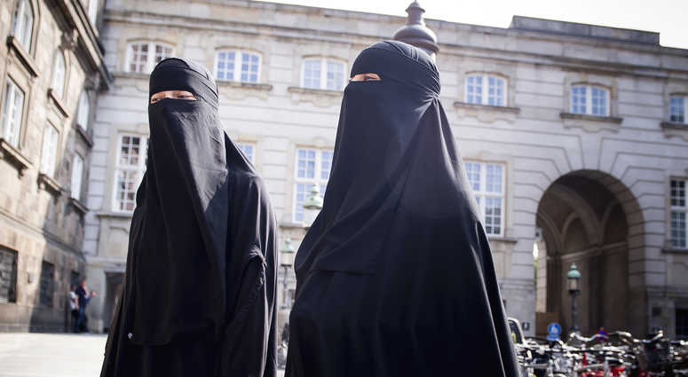 Women in niqab walk, in front of the Danish Parliament at Christiansborg Castle, in Copenhagen, Denmark, Thursday May 31. 2018.