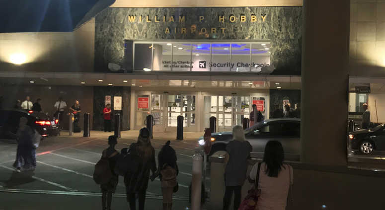 People wait outside Houston's William P. Hobby Airport on Thursday, June 7, 2018, after a toy grenade in a passenger's bag forced the shutdown of a security checkpoint, inconveniencing hundreds of people catching early-morning flights.