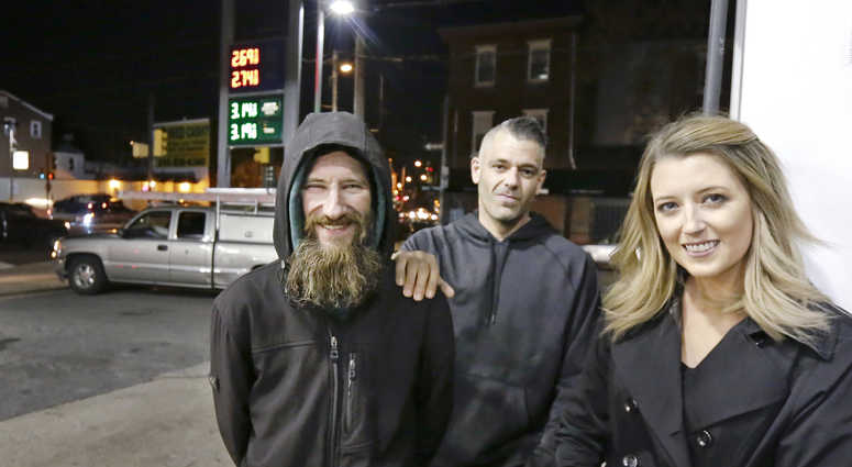 In this Nov. 17, 2017, file photo, Johnny Bobbitt Jr., left, Kate McClure, right, and McClure's boyfriend Mark D'Amico pose at a Citgo station in Philadelphia.