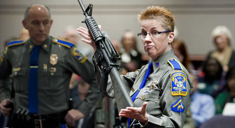 firearms training unit Detective Barbara J. Mattson, of the Connecticut State Police, holds a Bushmaster AR-15 rifle