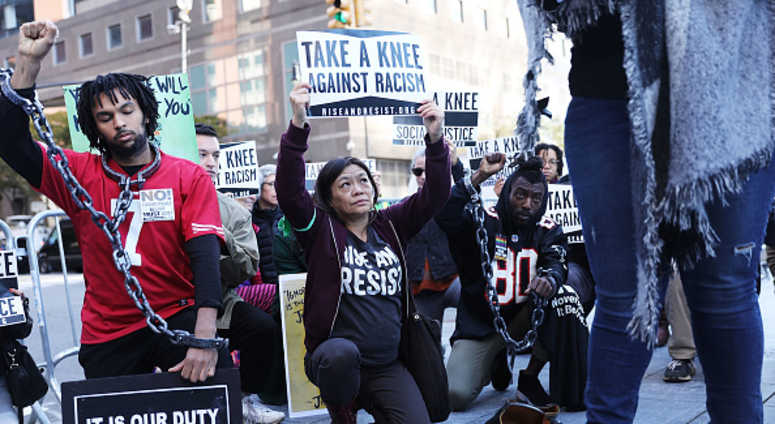 A coalition of advocacy groups 'take a knee' outside of a hotel where the quarterly NFL league meetings are being held