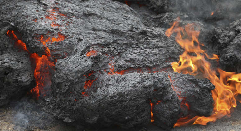 In this May 5, 2018, file photo, lava burns across a road in the Leilani Estates subdivision near Pahoa, Hawaii. The lava hisses, crackles and pops. It roars like an engine as it sloshes and bubbles.
